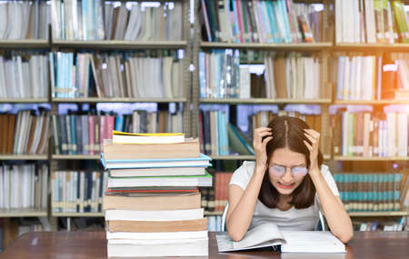 Foto de Young Girl Student with Glasses Reading book Overlap Serious, Hard Exam, Quiz, Test Sleeping headache worry in Classroom Education Library University Knowledge center - Imagen libre de derechos