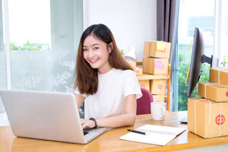 Foto de Young asian girl freelancer business private working at home office with laptop, note, coffee, packaging delivery online market on purchase orders to customer. - Imagen libre de derechos