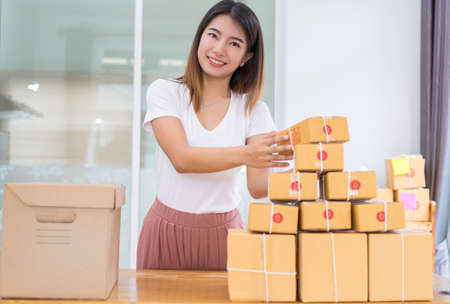 Foto de Young asian girl freelancer business private working at home office with laptop, note, coffee, packaging sort box delivery online market on purchase orders to customer. - Imagen libre de derechos