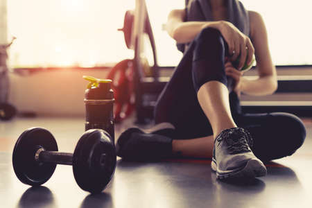 Foto de Woman exercise workout in gym fitness breaking relax holding apple fruit after training sport with dumbbell and protein shake bottle healthy lifestyle bodybuilding. - Imagen libre de derechos