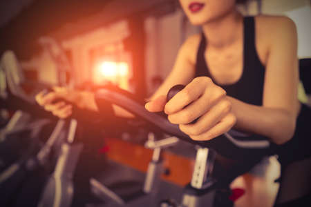 Photo pour Exercise bike cardio workout at fitness gym of woman taking weight loss with machine aerobic for slim and firm healthy in the morning. - image libre de droit