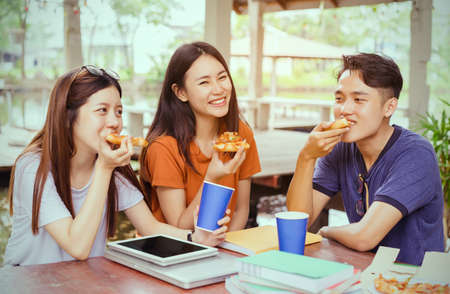 Photo pour Students asian group together eating pizza in breaking time early next study class having fun and enjoy party italian food slice with cheese delicious at university outdoor - image libre de droit