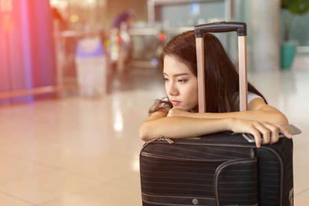 Photo pour Asian woman waiting flight delay in airport hall her bored sitting wait long time early morning with baggage suitcase for travel transport - image libre de droit