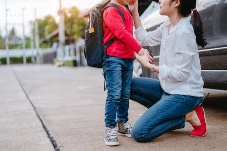 Photo pour Mother dressing up a son and sending to school, Parent and pupil going to kindergarten of preschool first day back to school concept. - image libre de droit