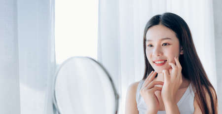 Photo pour Young Beauty Asian Woman Looking at Mirror Check Clear Face Skincare and Smile Morning in White Bedroom, Crop for Web Banner Panoramic. - image libre de droit