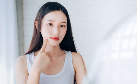 Foto de Young Asian woman squeeze acne problem face looking at mirror her without Skincare. - Imagen libre de derechos