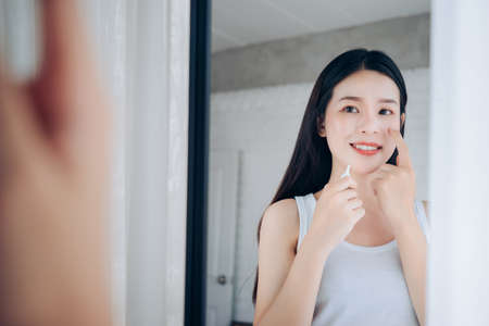 Photo for Beauty Asian Woman use Acne Gel Skincare after Cleansing on Face His Happiness and Look at mirror in White Bedroom. - Royalty Free Image