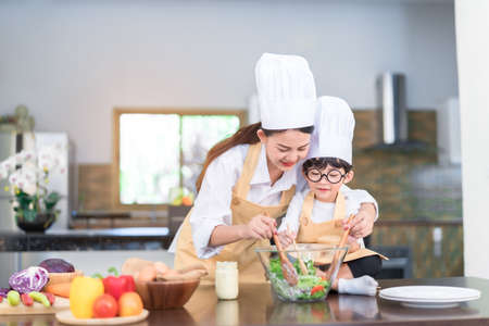 Foto de Professional Chef asian mom teaching little son cooking salad vegetable prepare healthy food in the kitchen room for dinner at home happy family lifestyle. - Imagen libre de derechos