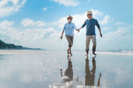 Photo pour Asian couple senior elder retire resting relax walking running at sunset beach honeymoon family together happiness people lifestyle - image libre de droit
