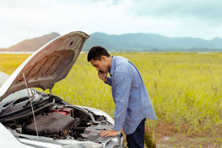 Photo pour Problem Car of male calling maintenance service assistance emergency between road trip journey in mountain lake river for examining and repair system engine fixing, Transportation travel lifestyle - image libre de droit