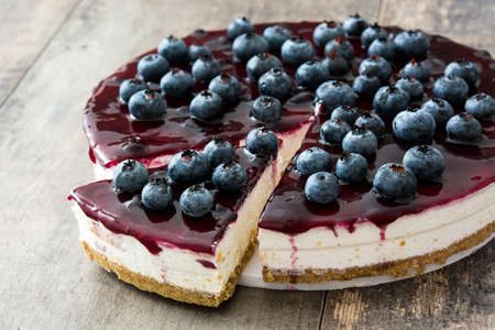 Photo for Blueberry cheesecake on wooden table - Royalty Free Image