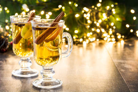 Foto de mulled cider in glass, ornaments and christmas light on wooden table - Imagen libre de derechos