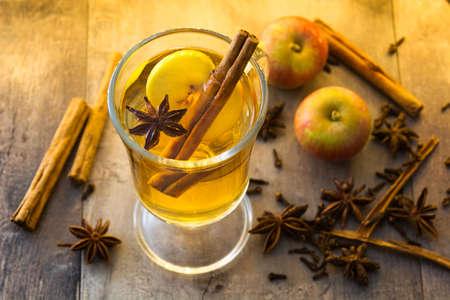 Foto de Mulled cider in glass on wooden table. Christmas drink - Imagen libre de derechos