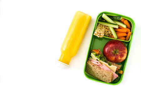 Foto de Healthy school lunch: Sandwich, vegetables, fruit and juice isolated on white background. Copyspace - Imagen libre de derechos