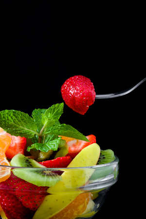 Foto de Strawberries on a spoon and assorted fruits in a bowl - Imagen libre de derechos