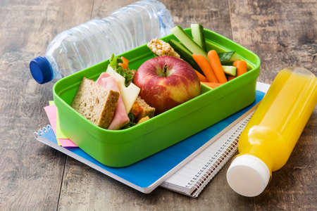 Foto de Healthy school lunch box: Sandwich, vegetables, fruit and juice on wooden table - Imagen libre de derechos