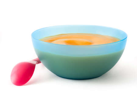 Foto de Baby food: blue bowl with fruit puree isolated on white background - Imagen libre de derechos