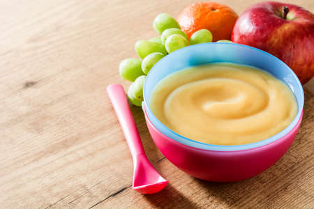 Foto de Baby food: colorful bowl of fruit puree on wooden table. Copyspace - Imagen libre de derechos