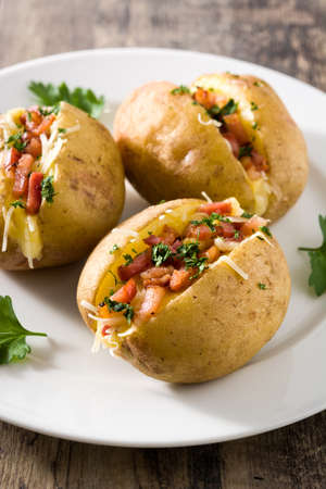 Foto de Stuffed potatoes with bacon and cheese on plate on wooden table. Close up - Imagen libre de derechos