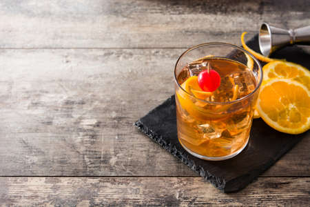 Photo for Old fashioned cocktail with orange and cherry on wooden table. Copyspace - Royalty Free Image