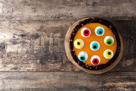 Foto per Halloween cake with candy eyes decoration on wooden table. Top view. Copy space - Immagine Royalty Free