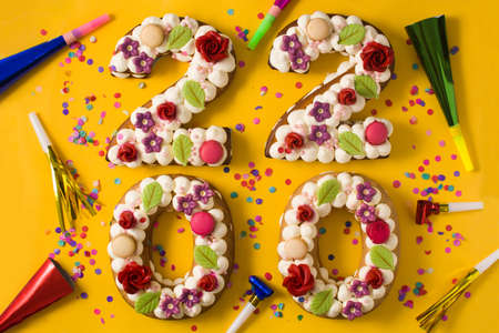 Photo pour 2020 cake and ornaments on yellow background. New year concept. - image libre de droit