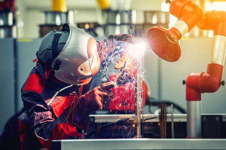 Foto de Industrial welder worker is welding metal part in factory with protective mask welding metal. vintage film grain filter effect styles - Imagen libre de derechos