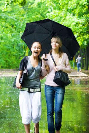Two girls rejoice to rainy weather.