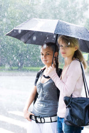 Two women in a riany weather.