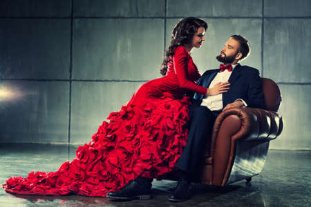 Photo for Young elegant loving couple in evening dress portrait. Woman in red and man in black suit sitting on chair. - Royalty Free Image