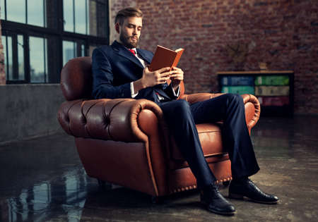 Photo for Young handsome businessman with beard in black suit sitting on chair reading book. Focus on face. - Royalty Free Image