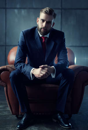 Photo for Young handsome businessman with beard in black suit sitting on chair and listens attentively to speaker. - Royalty Free Image