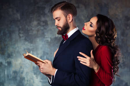 Photo pour Young elegant couple in evening dress portrait. Man reading book and woman trying to attract and embrace him. - image libre de droit