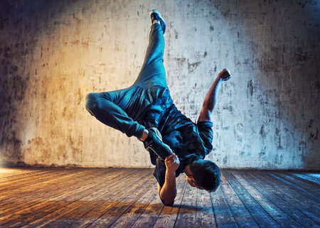 Photo pour Young man break dancing on wall background. Blue and red lights effect. - image libre de droit
