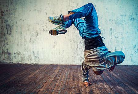 Foto de Young man break dancing on wall background. Vibrant colors effect. - Imagen libre de derechos