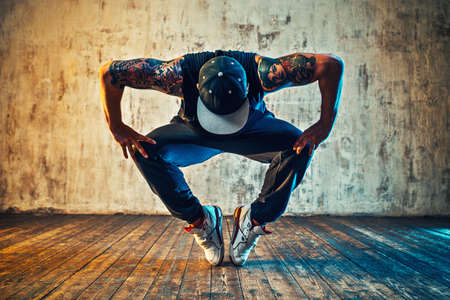 Photo for Young man break dancing on wall background. Blue and yellow colors tint. Tattoo on body. - Royalty Free Image