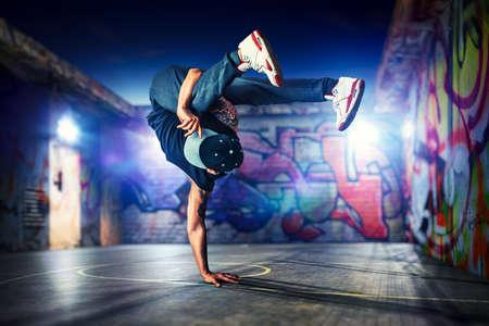Foto de Young man break dancing at night on urban painted walls background - Imagen libre de derechos