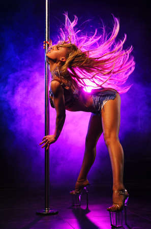 Photo for Young sexy slim woman pole dancing in dark club interior with lights and smoke - Royalty Free Image