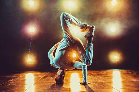 Foto de Young man break dancing in club with lights and smoke. Warm colors. - Imagen libre de derechos