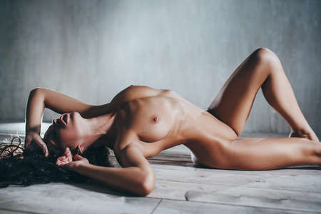 Photo for Young sexy nude brunette woman stretching on floor - Royalty Free Image
