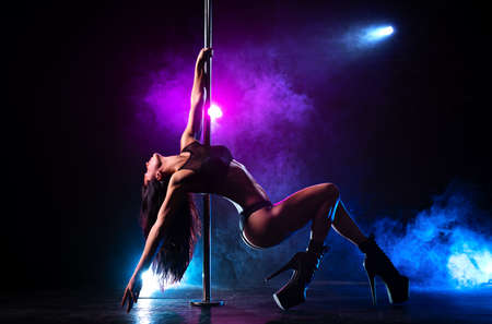 Photo for Young sexy slim brunette woman pole dancing in dark interior with smoke and lights - Royalty Free Image