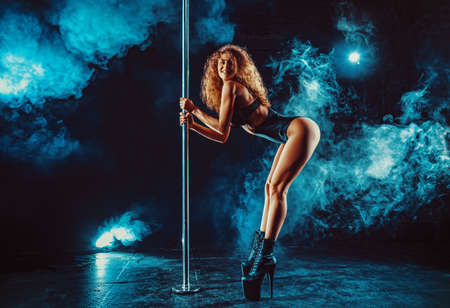 Photo for Young sexy slim blond woman pole dancing in dark interior with smoke and lights - Royalty Free Image