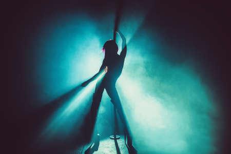 Photo pour Young sexy slim pole dance woman silhouette in smoke and blue light - image libre de droit