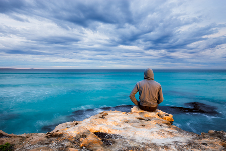 Photo pour A man sits on the edge of a rugged limestone cliff and looks over a stormy ocean view in South Australia. - image libre de droit