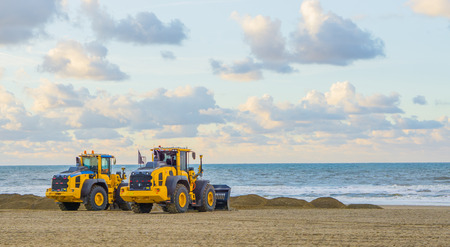 Photo pour earthmoving equipment machines working at the beach for maintenance moving sand industrial agriculture - image libre de droit
