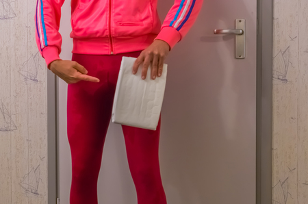 Photo pour young lady in a wet legging holding and pointing at a white adult diaper, urinary incontinence issues, embarrassing medical problems - image libre de droit