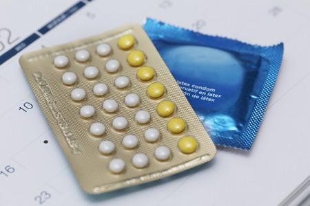 Foto de birth control pills and condom on a calendar - Imagen libre de derechos