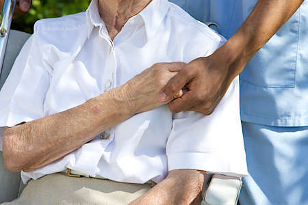Photo pour Symbol of comfort and support from care giver to elderly woman outdoor holding her hand - image libre de droit