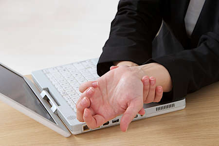 close up image of woman  with arthritis massaging hands in pain at office