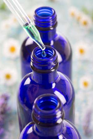 Foto de 3 Blue bottles of essential oil with flowers on background - Imagen libre de derechos